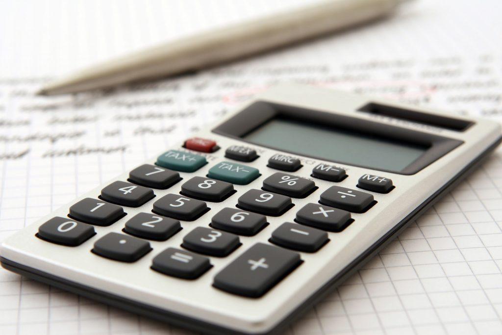 Nærbilde av kalkulator, penn og papir.